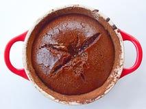 Smält chokladkaka på en röd gjutjärnpanna Royaltyfri Bild