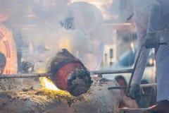 Smält guld som hälls in i Buddhastatyn, gjuter Arkivfoto