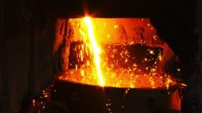 Smält metall flödar in i hinken arkivfilmer