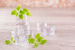 Smältande iskuber och mintkaramellsidor i små droppar av vatten Arkivbild