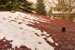 Smältande snö på det röda singeltaket Arkivfoton
