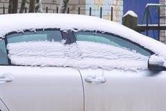 Smältande snö på taket och fönstren av bilen royaltyfria foton