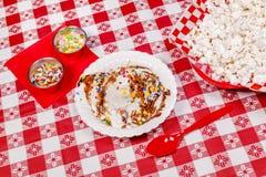 Smältande vaniljglass på picknicktabellen Arkivfoto