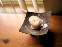 Smältt stearin på tappningmetallhållare på det Wood skrivbordet Arkivfoto