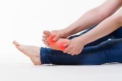 Smärta i ben för kvinna` s, massage av kvinnlig fot på vit bakgrund arkivbilder