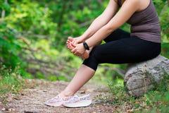 Smärta i foten för kvinna` s, massage av det kvinnliga benet, skada, medan köra, trauman under genomkörare royaltyfria foton