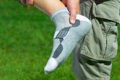Smärta i foten, fot på bakgrunden av grönt gräs Arkivfoto
