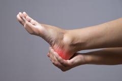 Smärta i foten Massage av kvinnlig fot Smärta i människokroppen på en grå bakgrund Royaltyfri Fotografi