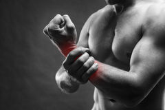 Smärta i handen muskulös huvuddelmanlig Stilig kroppsbyggare som poserar på grå bakgrund royaltyfri bild