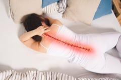 Smärta i ryggen, kvinna med ryggvärk hemma, tillbaka skadan royaltyfria bilder
