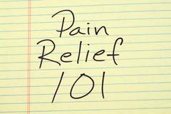 Smärta lättnad 101 på ett gult lagligt block Royaltyfri Foto