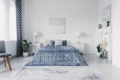 Smärta ovanför stor bekväm säng i lyxigt New York stilsovrum, verkligt foto arkivfoto