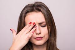 smärta Trött utmattat stressat kvinnalidande från det starka ögat Pain som isoleras på grå färger Stående av härlig ung kvinnlig  royaltyfri foto
