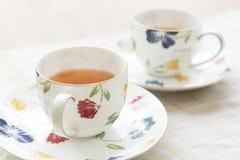 Smärtade härlig blomma två den keramiska kopp te och varmt te Royaltyfri Foto