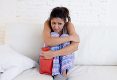 Smärtar den hållande varmvattenflaskan för den unga härliga latinamerikanska kvinnan mot buken som lider menstruations- period Royaltyfri Foto