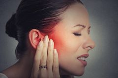 Smärtar den sjuka kvinnlign för sidoprofilen med örat det rörande smärtsamma huvudet arkivbild