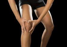 Smärtar det unga lidande för knäet för sportkvinnan innehavet sårat i ligamentskada eller dragen muskel fotografering för bildbyråer