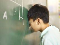 Smärtsam asiatisk elev som bankar hans huvud på svart tavla royaltyfria bilder