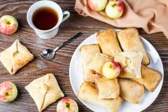 Små äppelpajer eller äppleomsättningar med kanel på en vit maträtt med tekoppen och mogna äpplen i bakgrund Arkivbilder