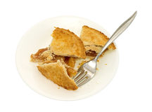 Små äppelpajstycken på plattan med gaffeln Arkivfoton