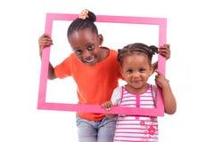 Små afrikansk amerikanflickor som rymmer en bildram Fotografering för Bildbyråer