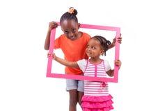 Små afrikansk amerikanflickor som rymmer en bildram Arkivfoto