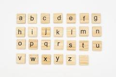 Små alfabetbokstäver trevar på träkvarter royaltyfri fotografi