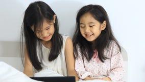 Små asiatiska flickor som skrattar med minnestavlan lager videofilmer