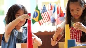 Små asiatiska flickor som staplar montessorikvarter lager videofilmer