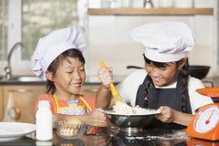Små asiatiska flickor som stiring det vetemjöl och ägget Arkivbilder