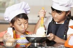 Små asiatiska flickor som stiring det vetemjöl och ägget Royaltyfri Bild