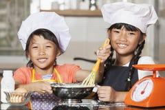 Små asiatiska flickor som stiring det vetemjöl och ägget Royaltyfri Fotografi