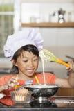 Små asiatiska flickor som stiring det vetemjöl och ägget Royaltyfria Foton