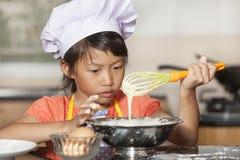 Små asiatiska flickor som stiring det vetemjöl och ägget Arkivfoto