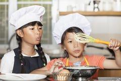 Små asiatiska flickor som stiring det vetemjöl och ägget Arkivfoton