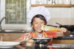 Små asiatiska flickor som stiring det vetemjöl och ägget Royaltyfria Bilder