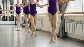 Små balettdansörer öva battementtendu under kurs i balettskola Ljusa bodysuits, vit pointe arkivfilmer