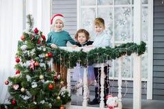 Små barn i förväntan av det nya året och jul Tre lilla ungar har gyckel och spelar nära julgranen royaltyfria bilder
