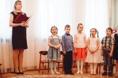 Små barn i härliga dräkter firar festmåltiden av våren i dagis royaltyfria foton