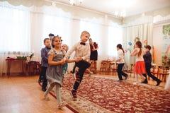 Små barn i härliga dräkter firar internationella kvinnors dag arkivfoton