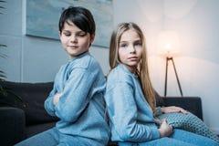 Små barn i pyjamas som tillbaka sitter för att dra tillbaka hemma Arkivfoto