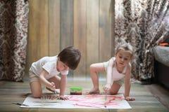 Små barn målar på ett stort ark av papper fotografering för bildbyråer