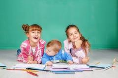 Små barn skriver, drar och läser på golvet Begreppsnollan fotografering för bildbyråer