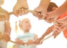 Små barn som rymmer repet på ljus bakgrund, fokus på händer arkivfoton