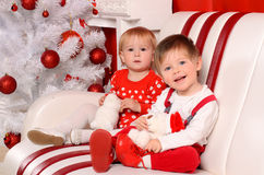 Små barn som sitter på julträdet royaltyfria bilder