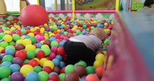 Små barn som spelar i pölen med plast- bollar i barnkammaren arkivfilmer