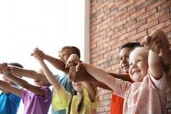 Små barn som tillsammans rymmer händer inomhus royaltyfri fotografi