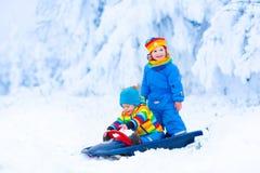 Små barn som tycker om en släderitt royaltyfri fotografi
