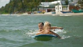 Små barn som tycker om havet som surfboarding på sommarsemester lager videofilmer