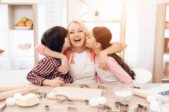 Små barnbarn kysser härligt farmorsammanträde i kök Stekheta kakor royaltyfri foto